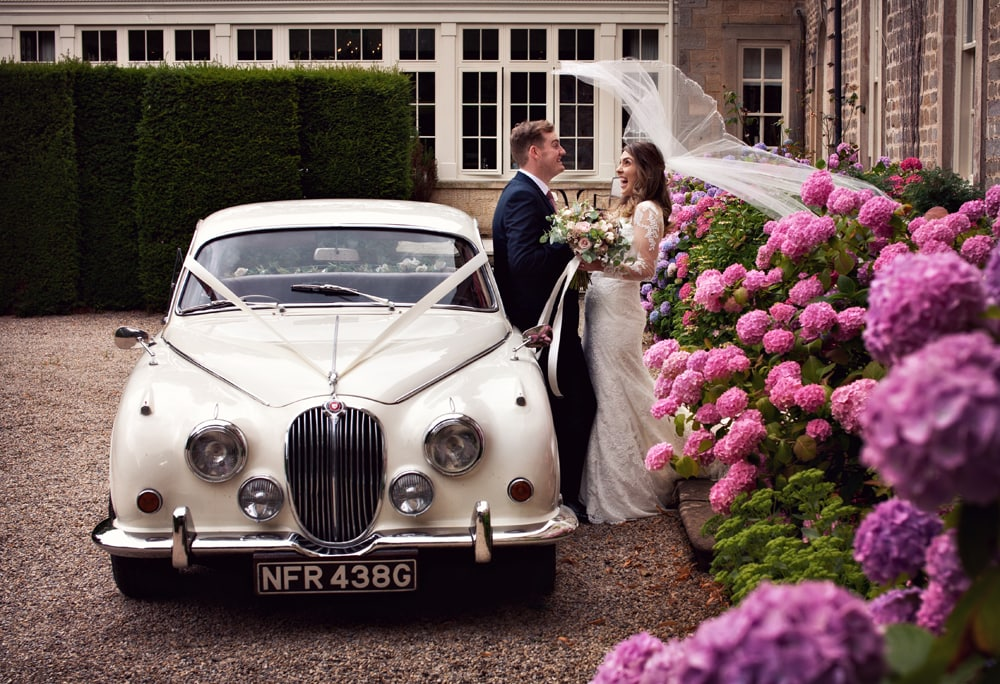 Bride and Groom leaning against a vintage Jaguar at Headlam Hall, the wind caught the brides veil and the couple are laughing.