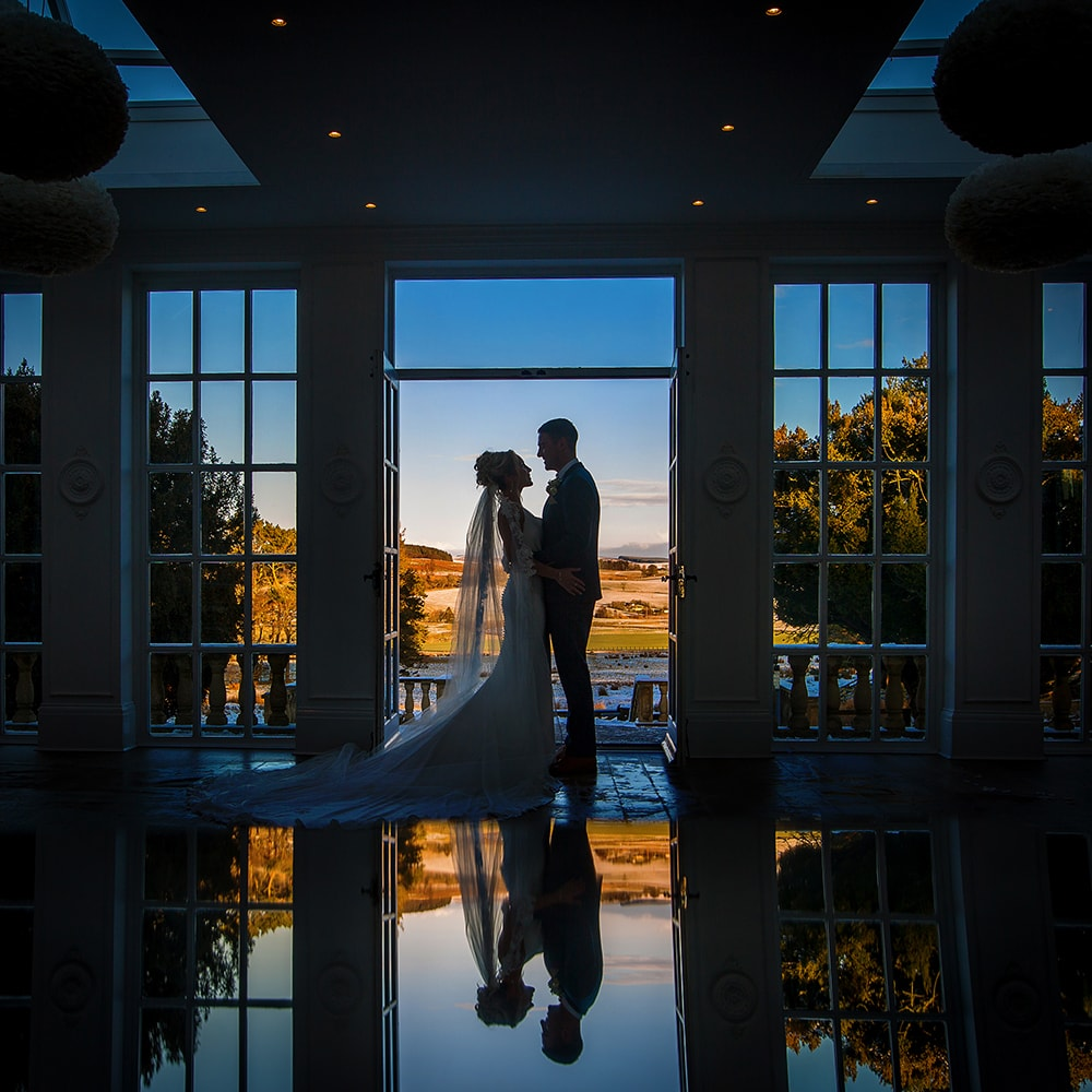Bride and Groom at Woodhill Hall, silhouette against a Winter blue sky, bride is holding onto the groom and they are looking at each other
