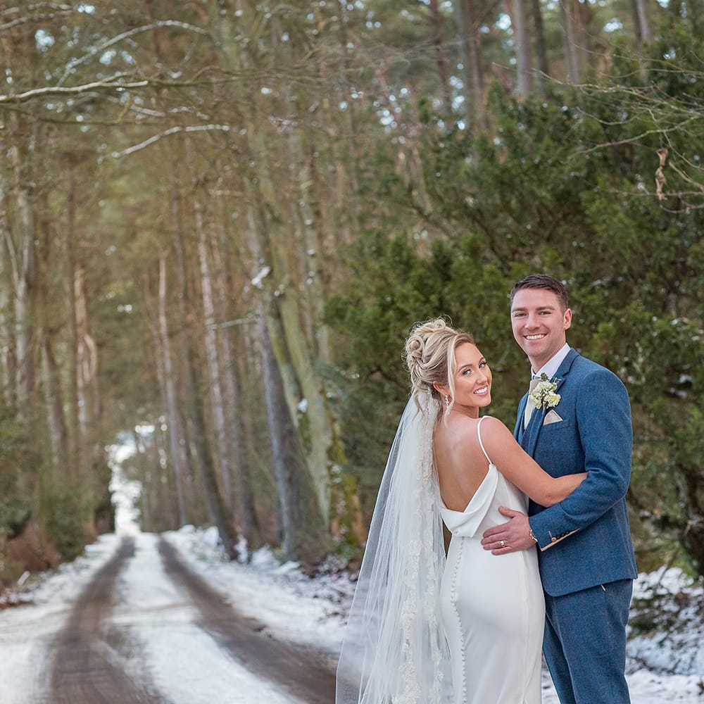 Bride looking over her shoulder and Groom looking at the camera, backdrop is a snow scene drive at Woodhill Hall, the drive is tree lined and the couple are hugging