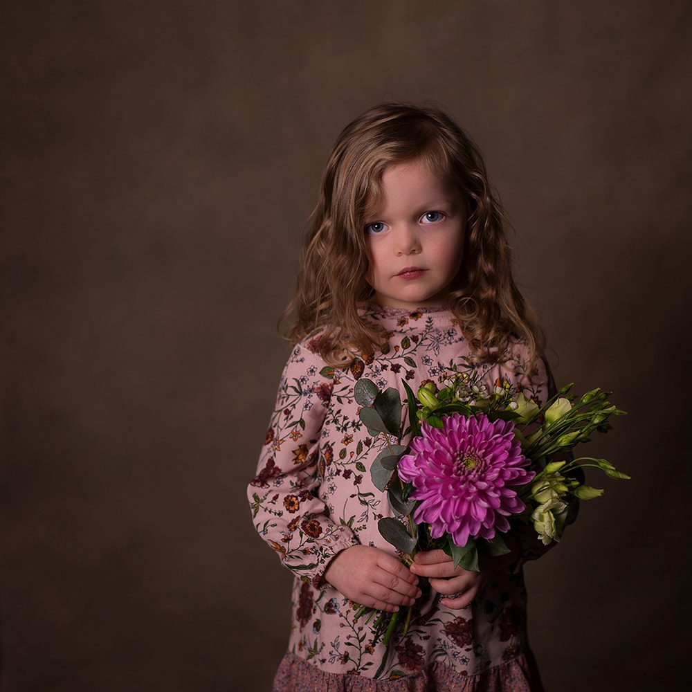 3 year old girl photographed in the studio holding a posie of flowers.