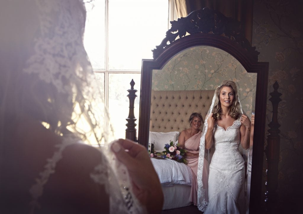 vintage toned image of bride and bridesmaid in bridal suite at Wynyard Hall