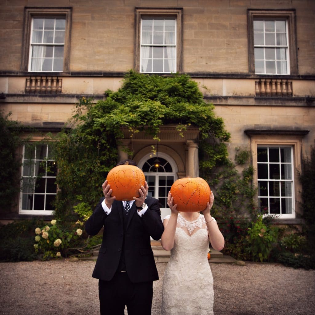 Bride and Groom at Middleton Lodge Holding pumpkins over their faces.