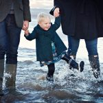 little girl splashing in the autumn sea holding mum and dad's hand