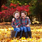 two boys laughing in autumn leaves