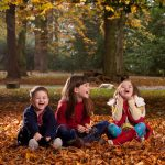 Three young children sat playing in the leaves at Crathorne Hall