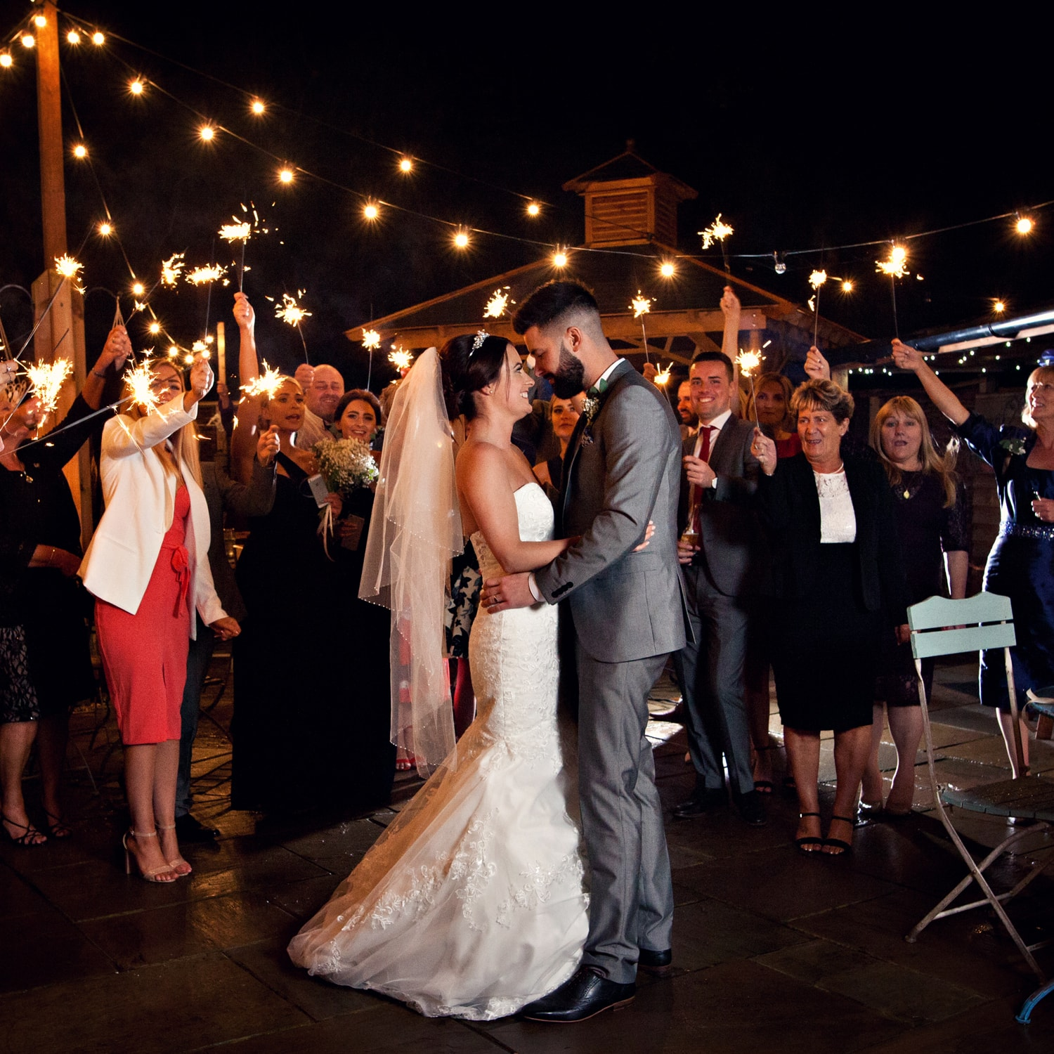 bride and groom in courtyard at whinstone view guests with sparklers