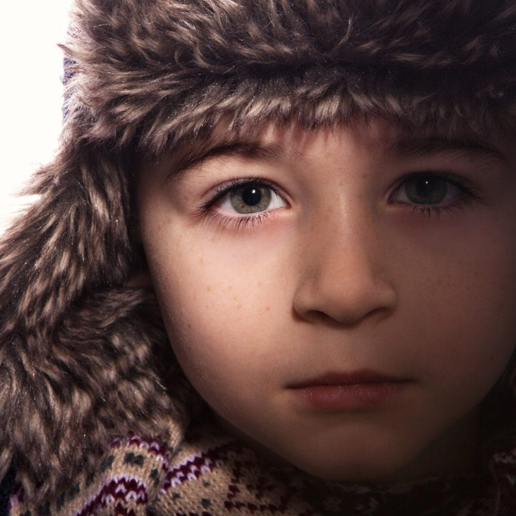 Studio portrait of young boy wearing a winter hat and cropped really close
