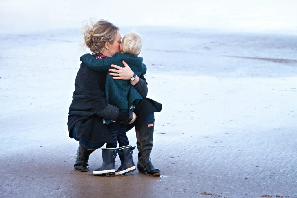 Mother and young daughter hugging on Saltburn beach image has a cool hue with a warm sentiment