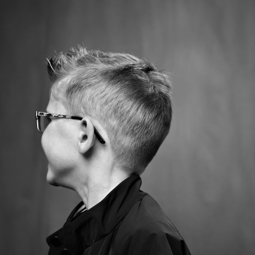 black and white headshot of young boy looking away in the studio