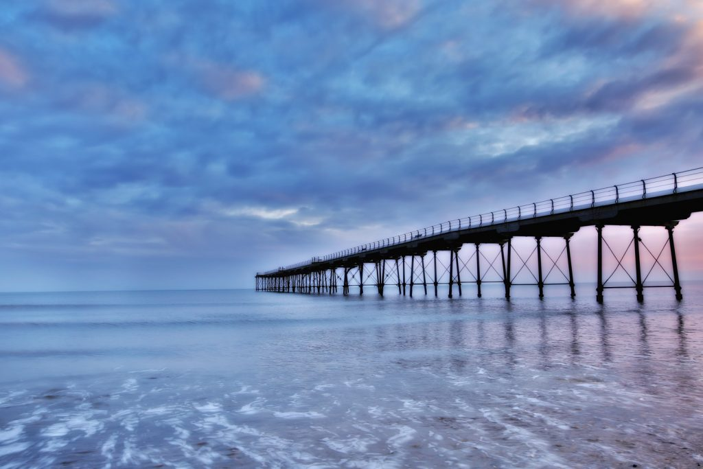 Early morning silhouette of Saltburn pier blurred waves