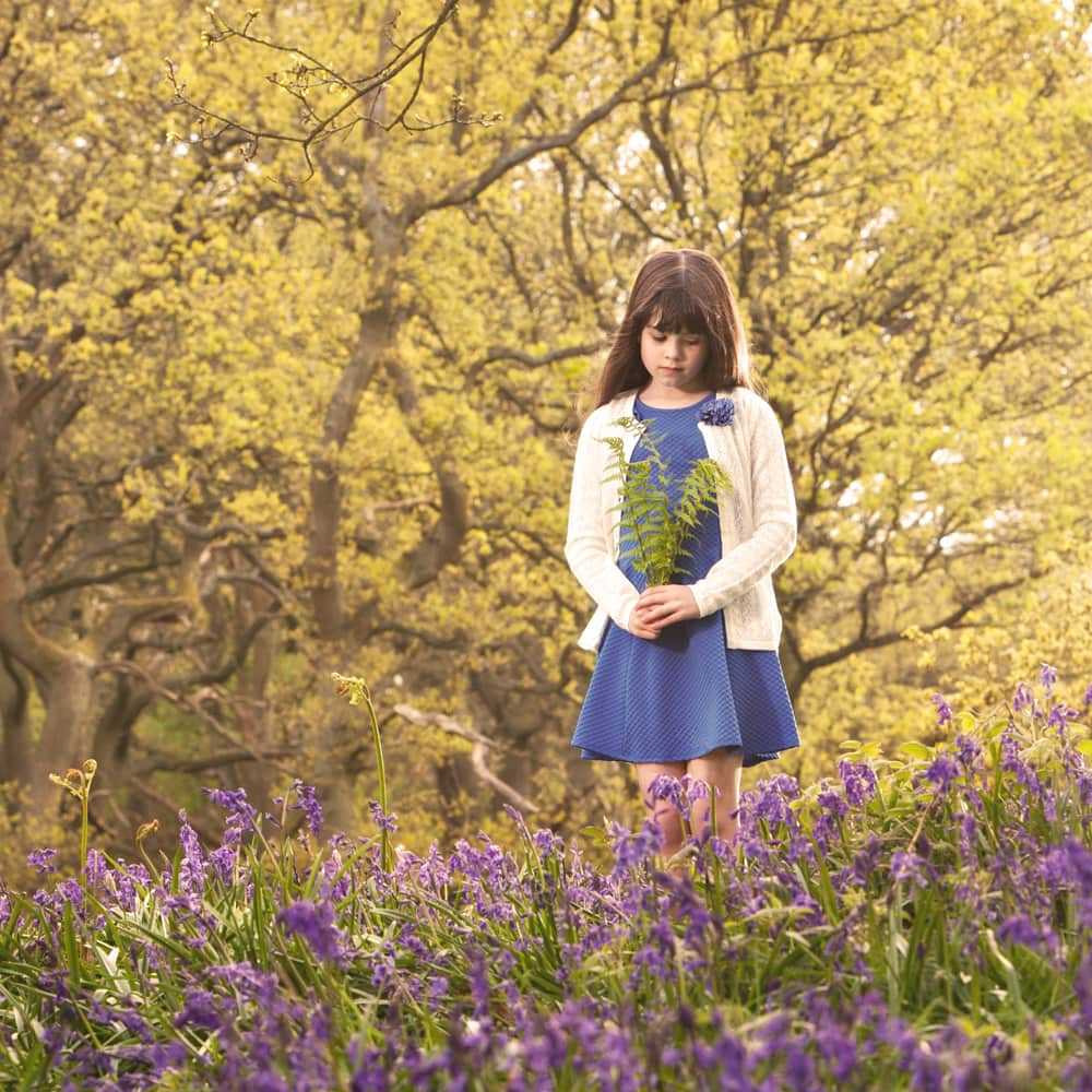 young lady photographed in Newton Wood holding fern and surrounded by bluebells