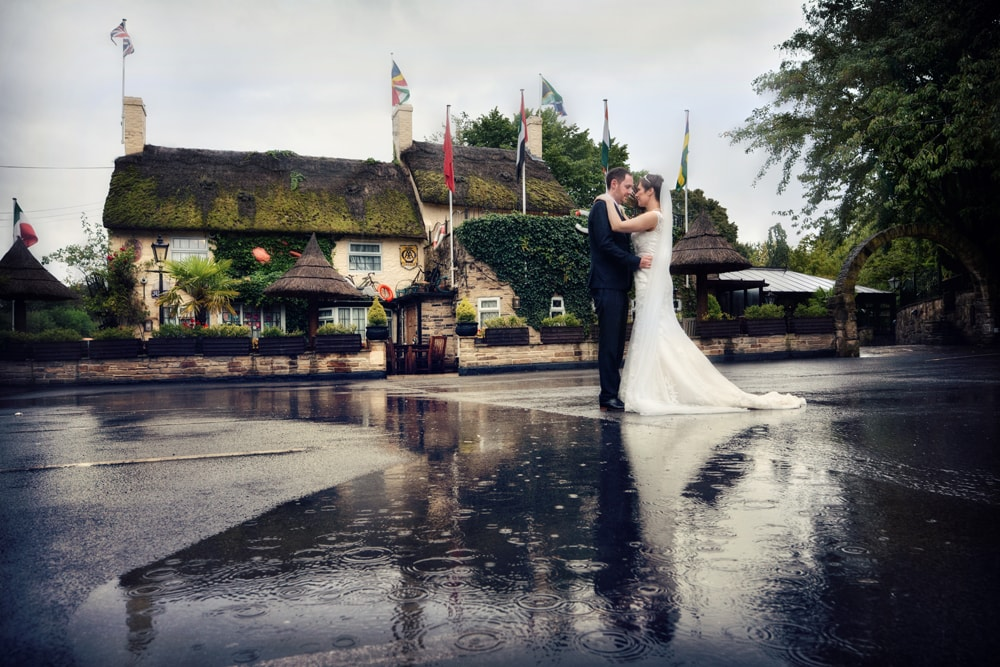 image of the bride and groom stood in the rain outside the crab and lobster