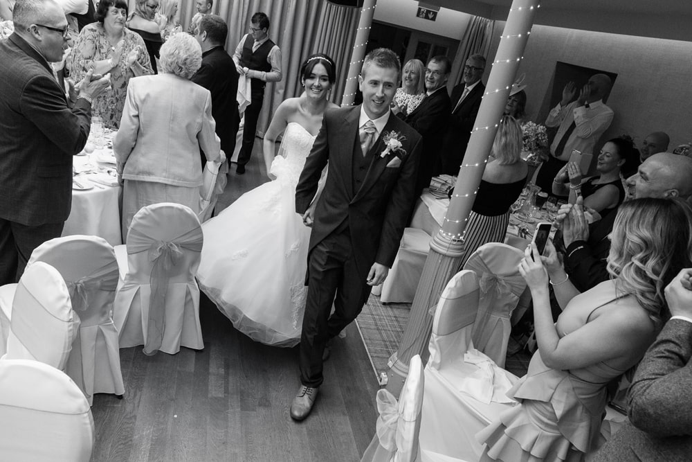black and white image of the bride and groom walking into the wedding reception room at Headlam Hall