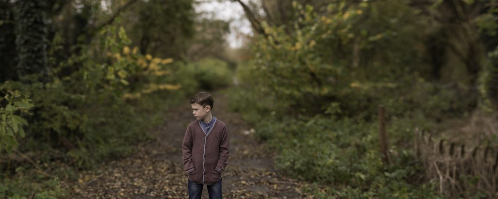 panoramic image of a young boy stood in the woods