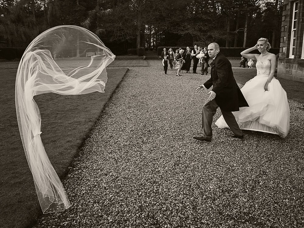 bride and groom black and white image taken at Crathorne Hall and the groom is chasing the brides viel which has blown off.