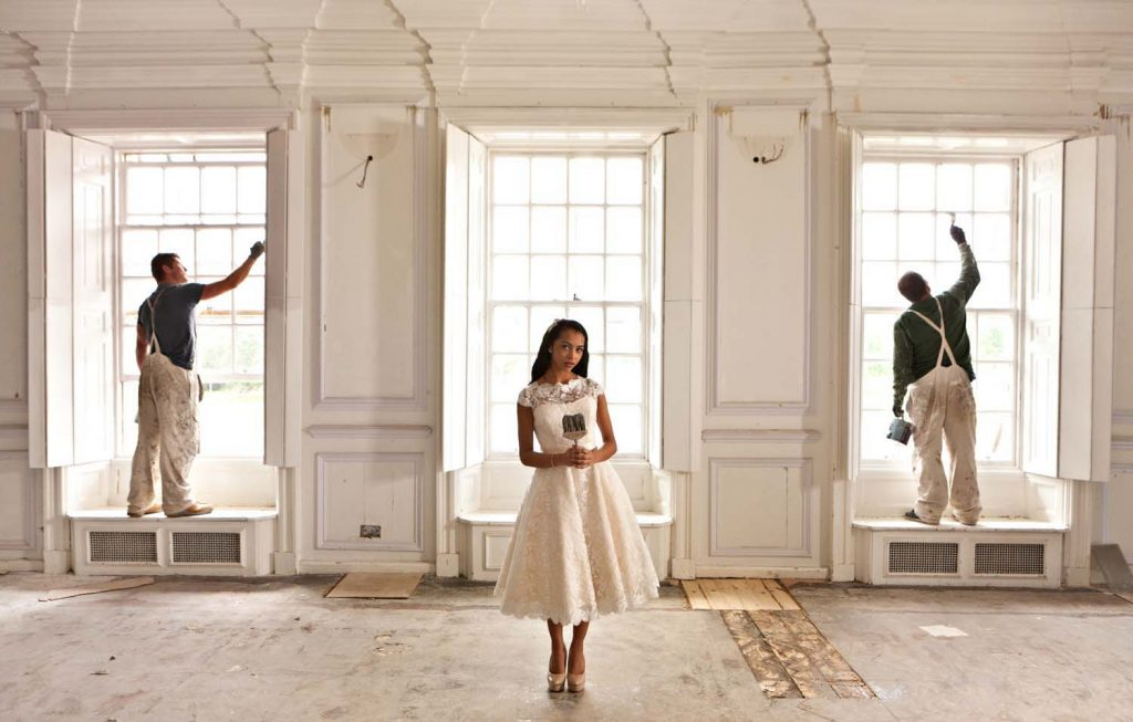 Acklam Hall wedding images of young bride holding a paint brush with the decorators finishing painting the room in the background.