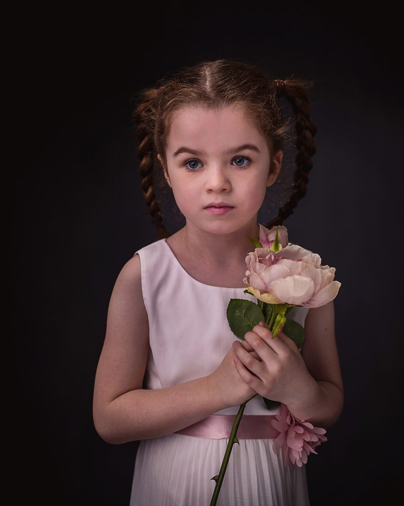 studio portrait of a young girl holding a silk rose with a timeless expression