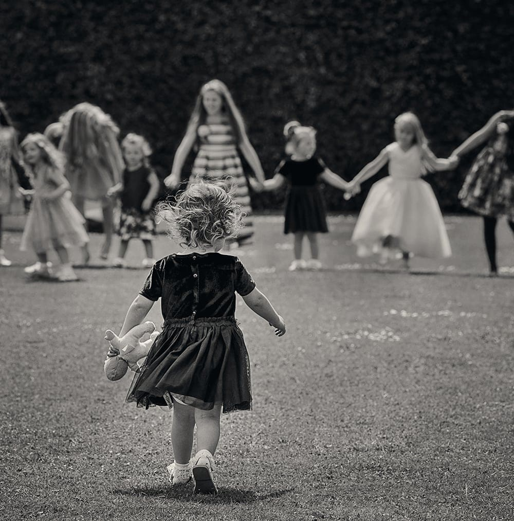 little girls running on the lawn at Headlam Hall in black and white