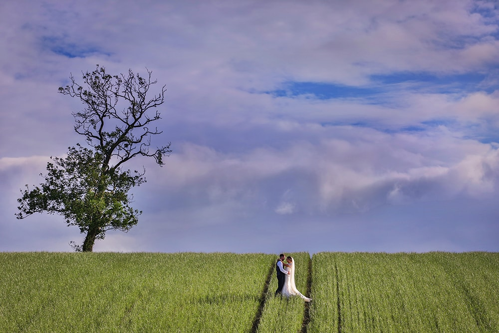 colour image of the bride and groom embracing in a field at the yorkshire wedding barn
