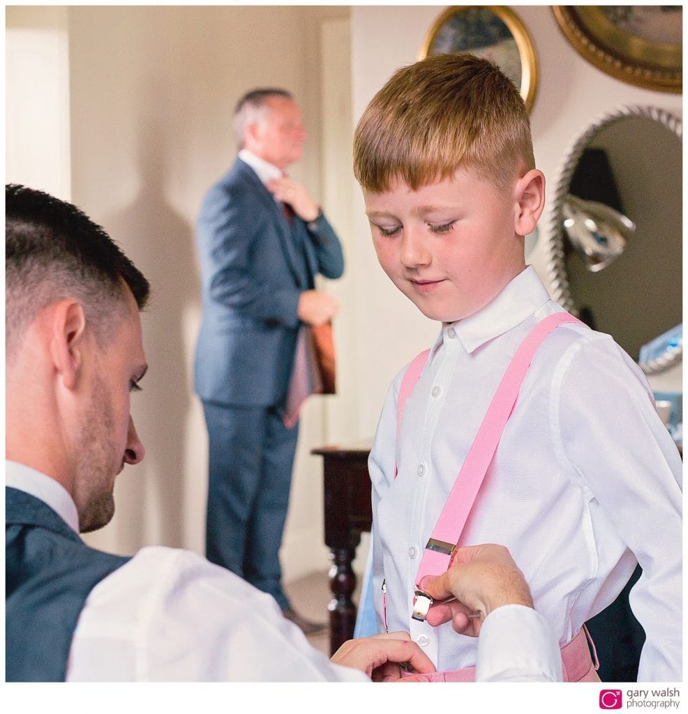 father and son getting ready for the wedding, grandad in the background checking his tie.