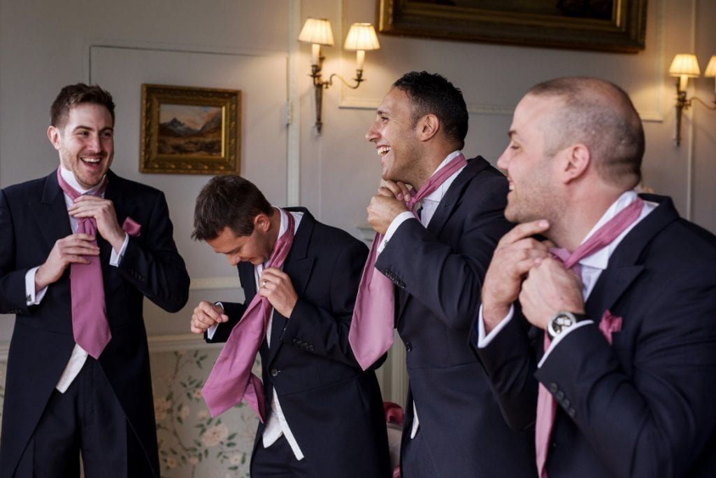 Groom and Groomsmen fastening ruche ties and laughing