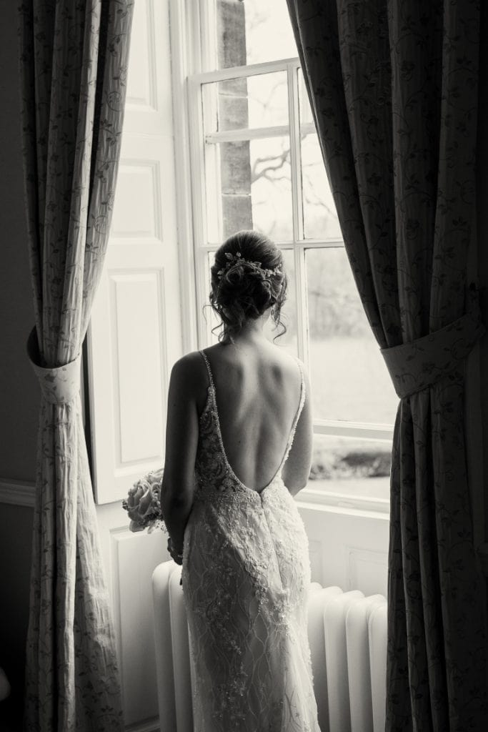 back view of the bride looking out of a window in black and white