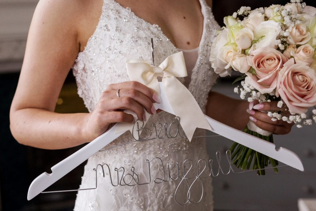 close up of coathanger with the brides married name being held with her bouquet