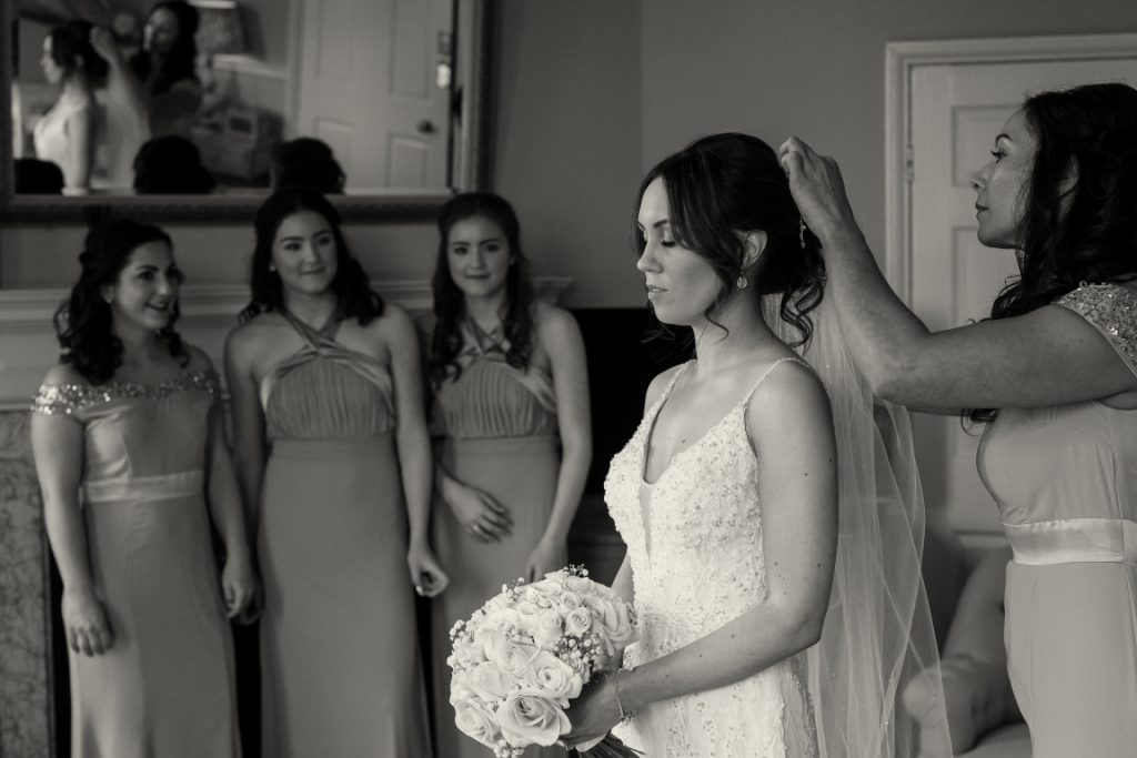 maid of honour putting the brides viel on with bridesmaids watching