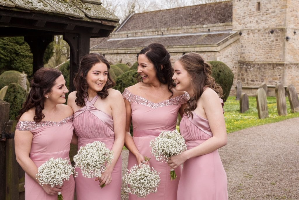 Bridesmaids laughing outside the church