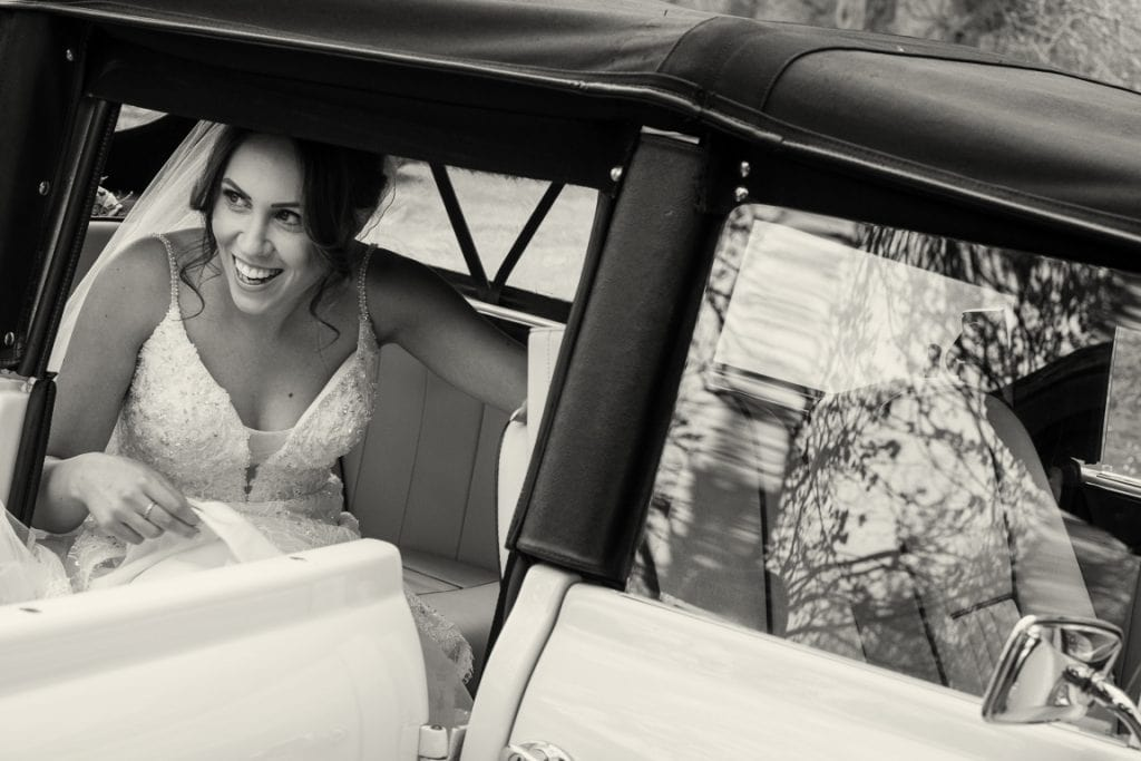 black and white image of the bride getting out of her wedding car