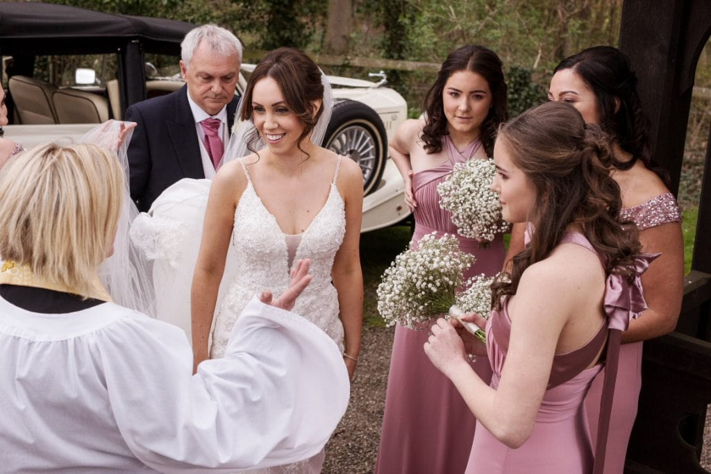 Vicar briefing the bride and her bridesmaids before the ceremony
