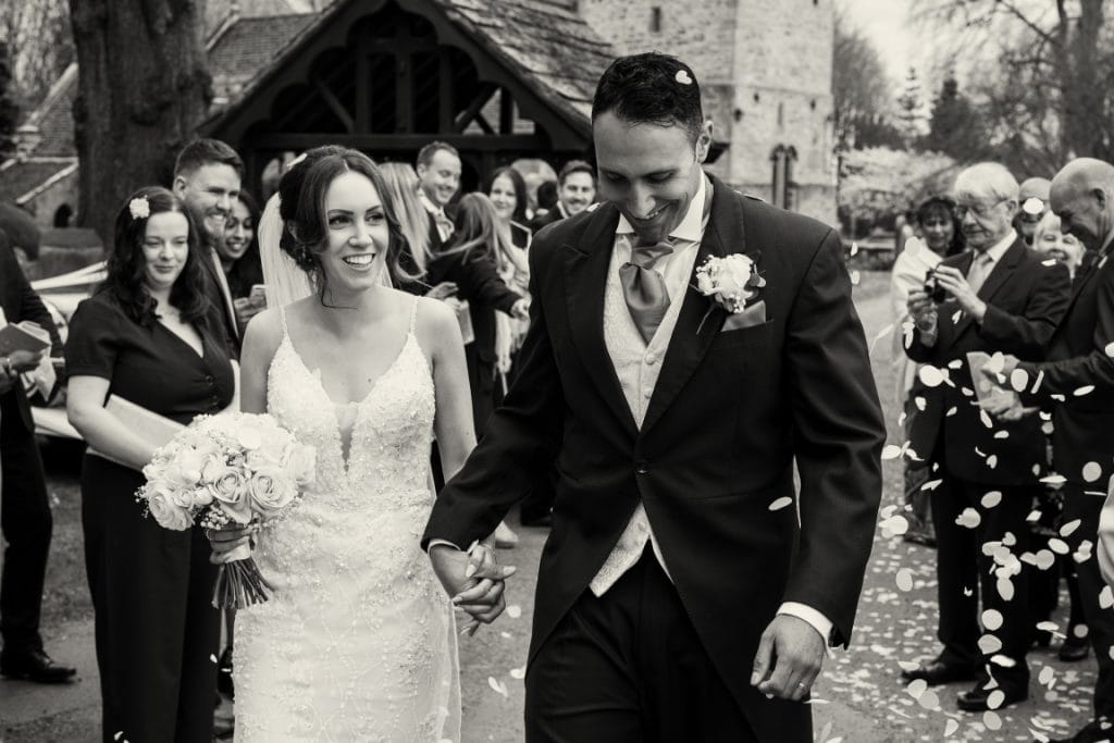 black and white confetti image of the bride and groom walking through the guests