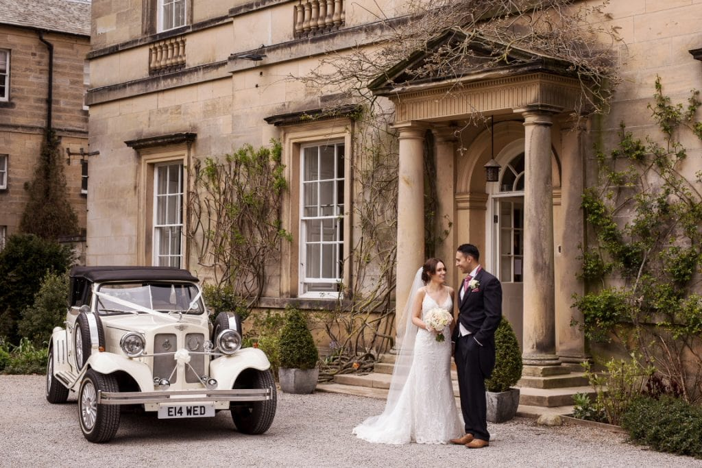 Bride and Groom at the front of Middleton Lodge with a vintage car
