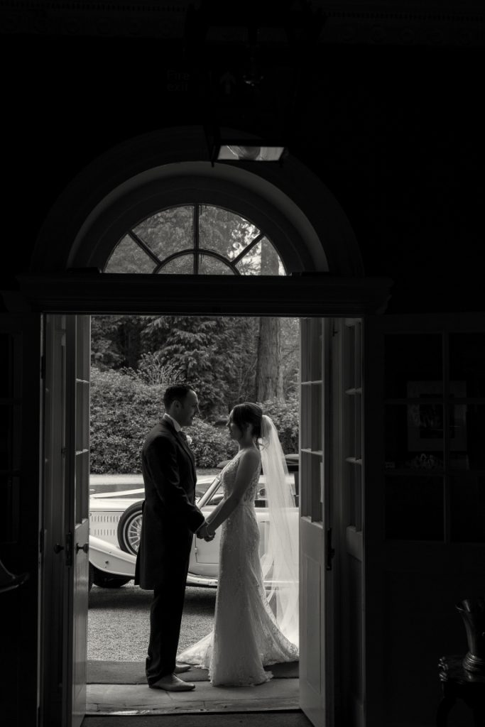 black and white image of the bride and groom silhouetted in the doorway at Middleton Lodge