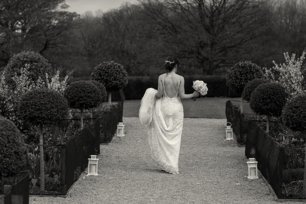 black and white image of the bride walking away