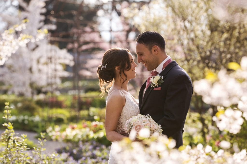 bride and groom hugging in a beautiful Spring garden