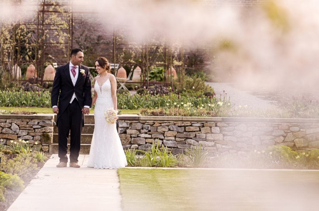bride and groom holding hands in a Spring garden