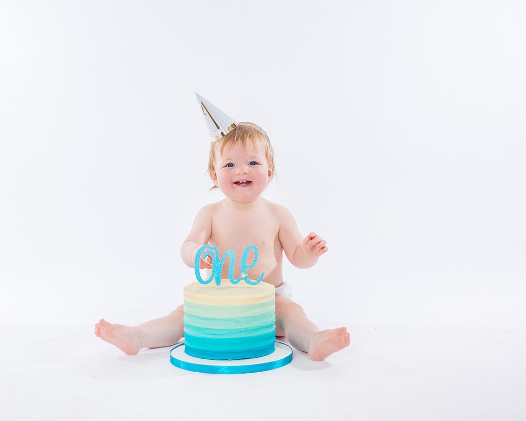 studio portrait of a little boy on his first birthday, he is sat on the floor wearing a party hat with a birthday cake between his legs and a huge swirly number one on top.