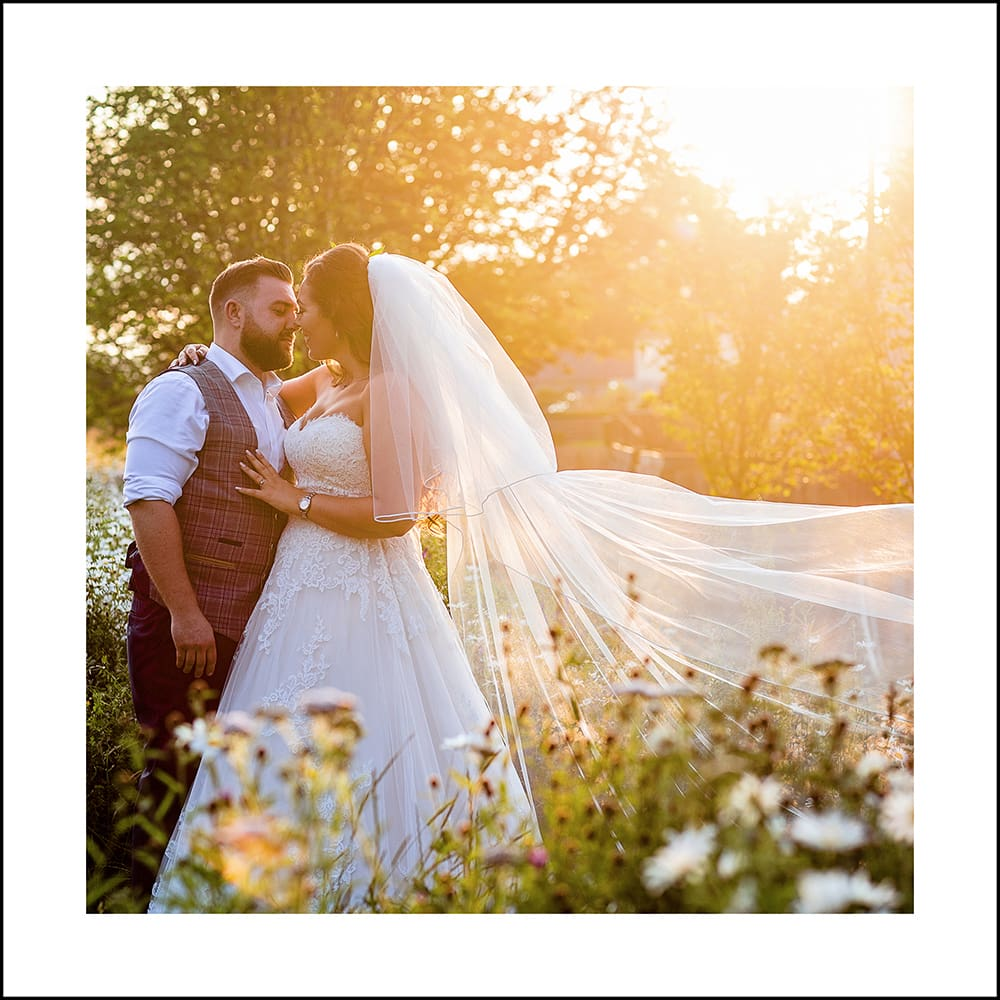 bride and groom at sunset, with the viel blowing at Le Petit Chateau