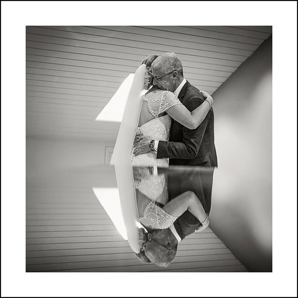 bland and white image of bride and dad hugging in the bridal suite at Yorkshire Wedding Barn
