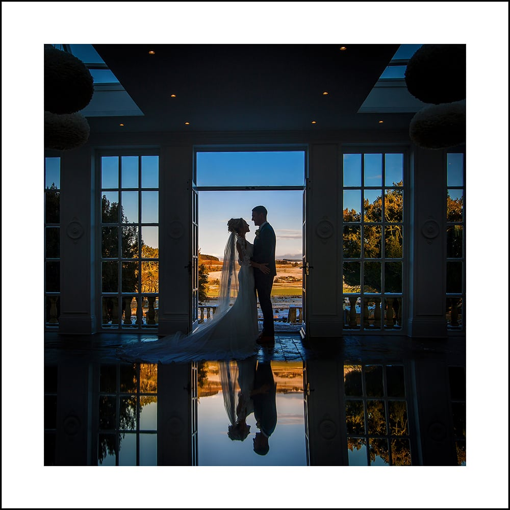 visual bride and groom silhouetted against a winter scene at Charlton Hall