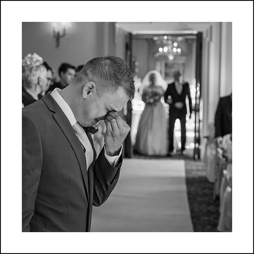 bride and dad entering the room at Crathorne Hall, groom in the foreground emotional