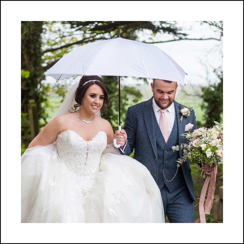 close up of bride and groom walking from church in the rain
