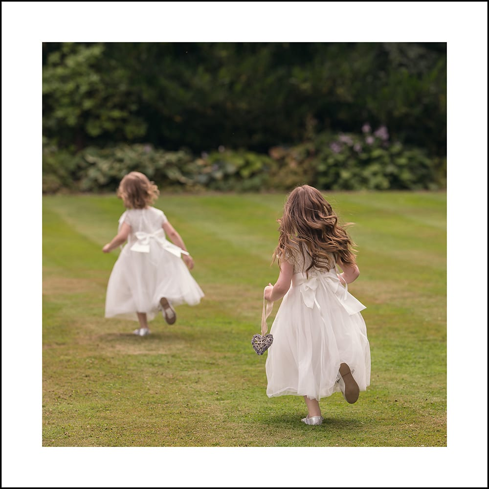 2 flowergirls running on the lawn at Lartington Hall