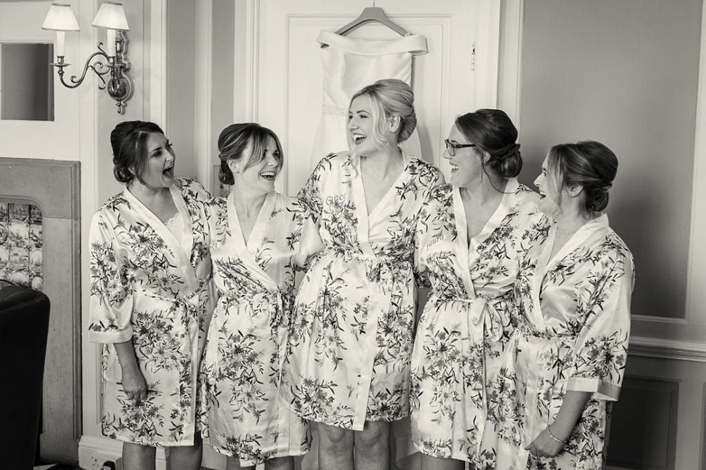 Headlam Hall black and white shot of the bride and bridesmaids in robes laughing