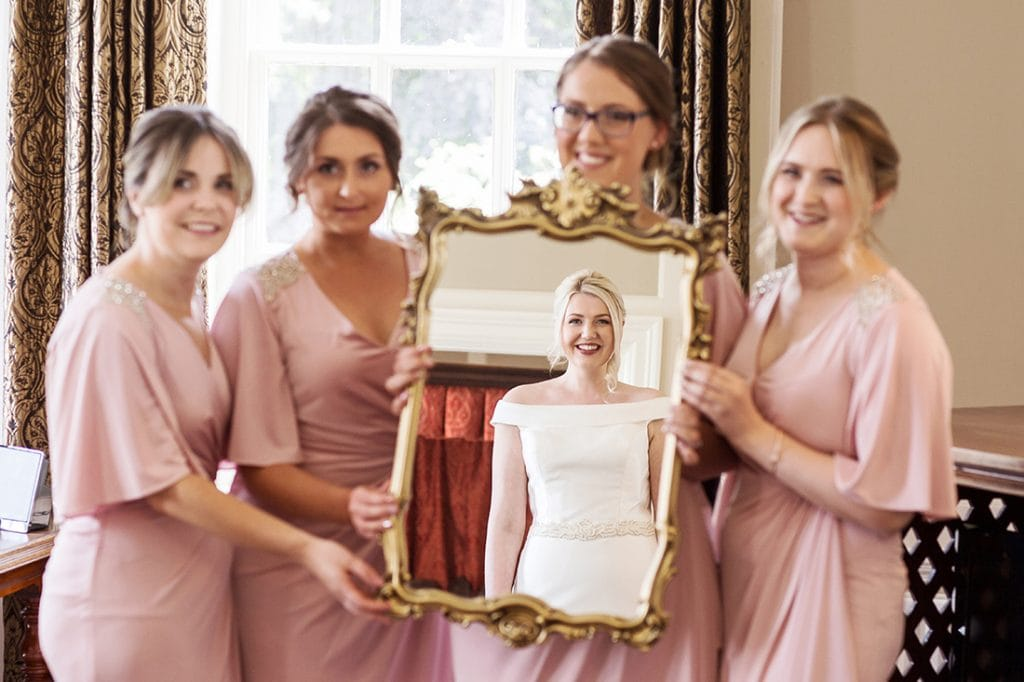 Headlam Hall bride looking at herself in the mirror held by her bridesmaids