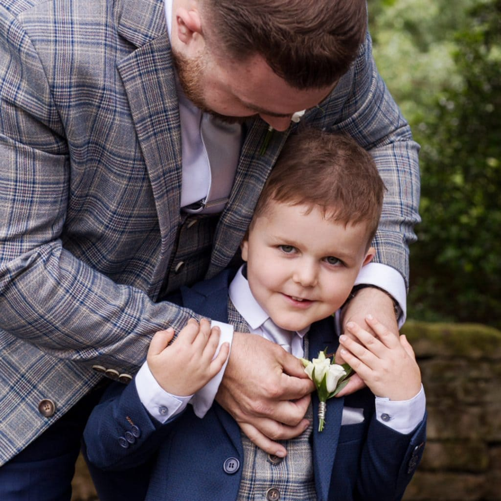groom helping his young son with his buttonhole