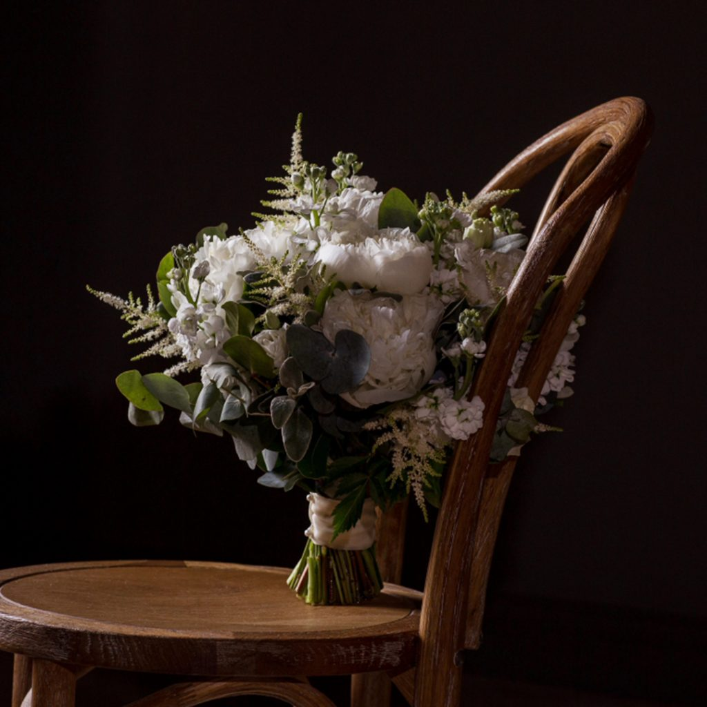 brides flower placed on old wooden chair