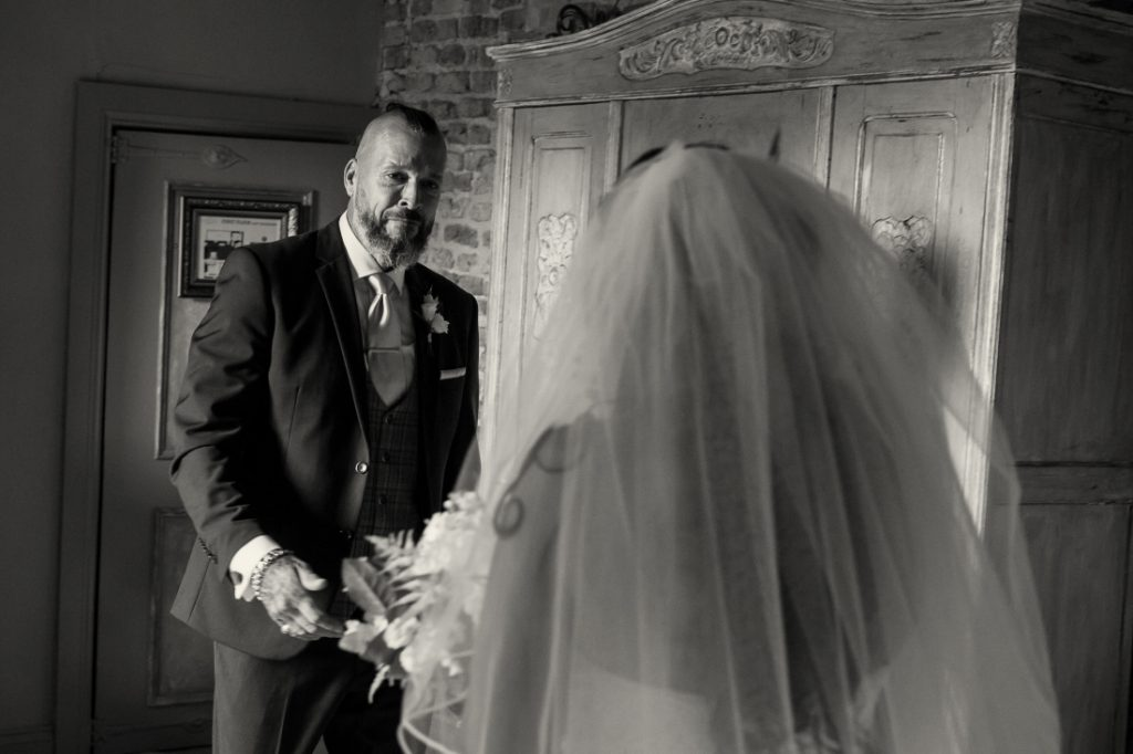 brides dad seeing his daughter in her dress for the first time