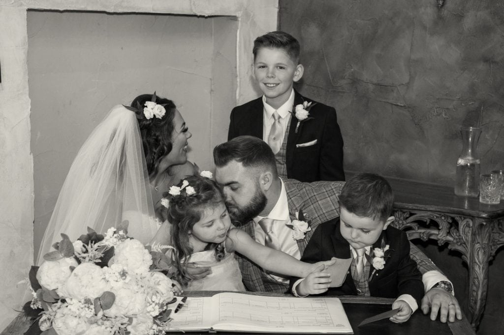 bride and groom and children signing wedding register